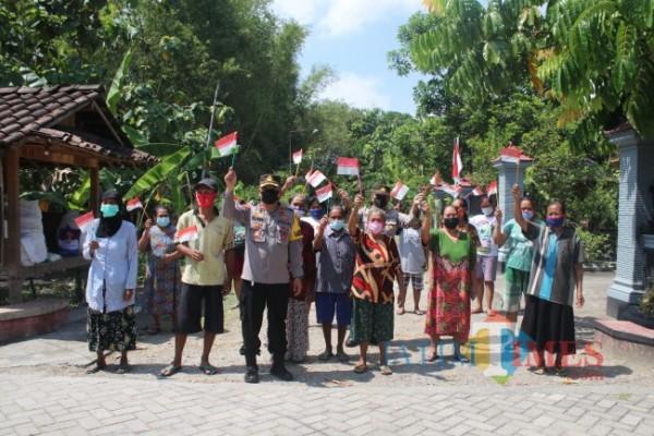 Usai membagikan bantuan sembako, Kabag Ops Polres Ngawi didampingi Kasubag Humas Polres Ngawi bersama anggota mengajak warga Desa Lego Kulon untuk bersama-sama mengibarkan replika bendera merah putih