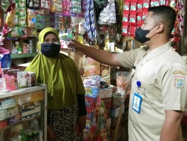 Pengecekan suhu tubuh salah satu pedagang pasar tradisional oleh petugas Disperindag Kabupaten Malang. (Foto: Riski Wijaya/MalangTIMES)