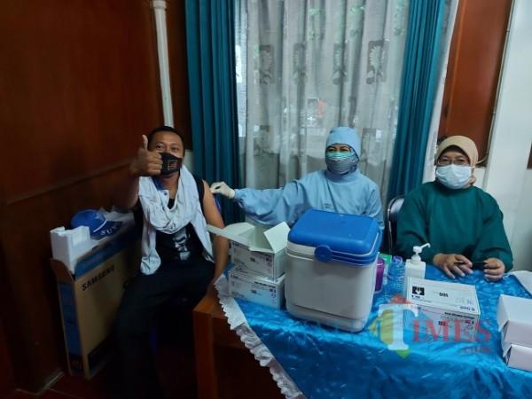 Salah satu supeltas bernama Didin yang merasa bahagia mendapatkan vaksin dosis kedua dari Polresta Malang Kota yang bekerjasama dengan Dinas Kesehatan Kota Malang, Selasa (2/8/2021). (Foto: Tubagus Achmad/MalangTIMES)