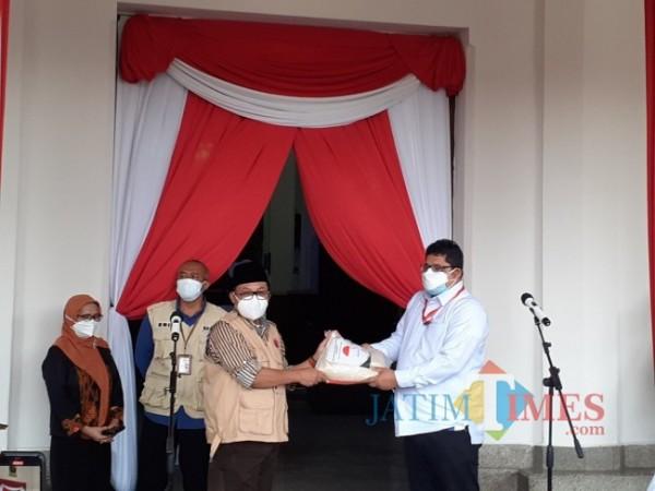 Wali Kota Malang Sutiaji (berkopiah) saat menerima simbolis bantuan paket beras dari Kemensos RI, Selasa (3/8/2021). (Arifina Cahyanti Firdausi/MalangTIMES).