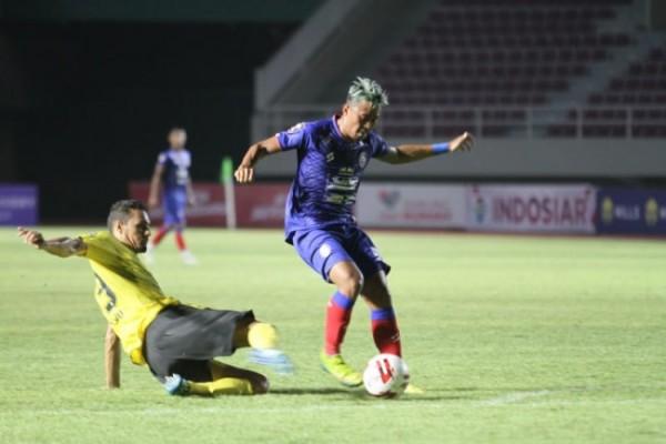Striker Arema FC, Kushedya Hari Yudo (jersey biru) saat melewati hadangan bek asing Barito Putera (foto: Arema FC for MalangTIMES)