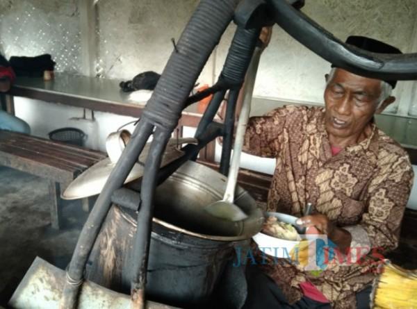 Sukadi, pemilik warung Soto Ndodok, saat menyajikan soto jualannya. (Foto: Riski Wijaya/MalangTIMES)