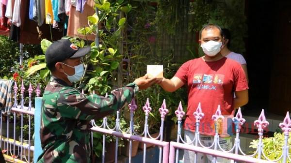 Para prajurit TNI Koramil 02 Kota Batu kodim 0818 Malang-Batu saat membagikan bantuan paket obat kepada warga isoman di Kecamatan Batu. (Foto: Irsya Richa/ MalangTIMES)