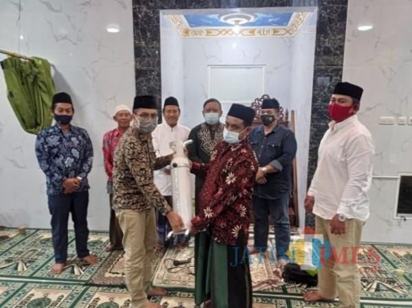 Direktur JatimTIMES, Lazuardi Firdaus (depan pakai peci) saat memberikan bantuan tabung oksigen untuk Masjid Babul Jannah (foto: Hendra Saputra/MalangTIMES)