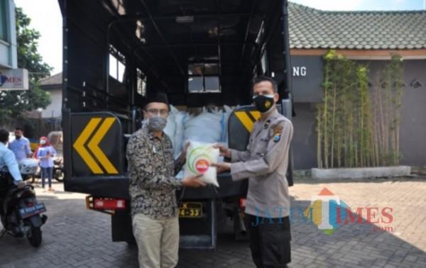 Direktur Jatim Times Lazuardi Firdaus saat menerima secara simbolis bantuan sembako dari Kapolresta Malang Kota (doc MalangTIMES)