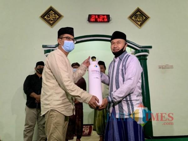Direktur JatimTIMES Lazuardi Firdaus saat menyerahkan bantuan tabung oksigen kepada takmir Masjid Baiturrahmah RT 4, RW 8, Dusun Jeding, Desa Junrejo, Kecamatan Junrejo, Kota Batu, Sabtu (14/8/2021) malam. (Foto: Irsya Richa/MalangTIMES)