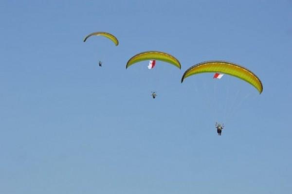 Atlet paralayang saat menerbangkan bendera merah putih di langit Kota Batu.
