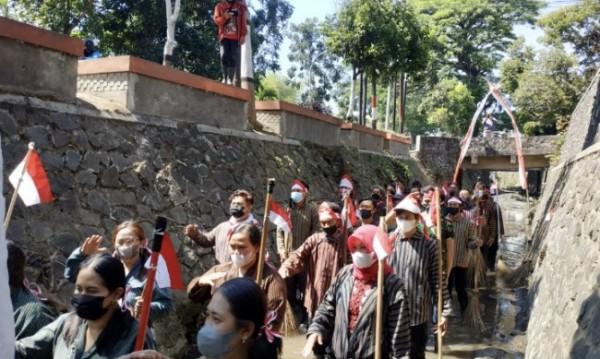 Beberapa orang saat melakukan upacara di sungai Jl Ir Soekarno, Kelurahan Dadaprejo, Kecamatan Junrejo, Selasa (17/8/2021). (Foto: Istimewa)