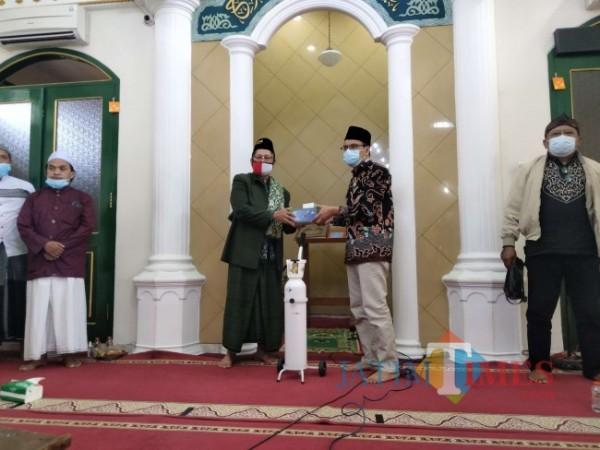 Direktur JatimTIMEs Lazuardi Firdaus saat secara simbolis menyerahkan bantuan dalam Gerakan Rumah Ibadah Bergerak di Masjid Taufiqurrahman Kota Malang.(Foto: Riski Wijaya/MalangTIMES).