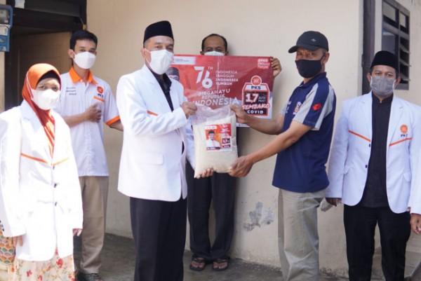 Ketua DPD PKS Kota Malang Ernanto Djoko Purnomo (dua dari kiri) saat menyerahkan bantuan sembako kepada warga di momen peringatan HUT RI ke-76. (Foto: Istimewa).