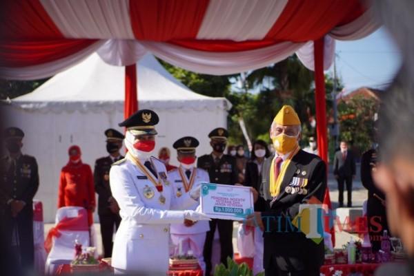 Secara simbolis insentif diberikan oleh Wali Kota Batu Dewanti Rumpoko kepada Ketua Legiun Veteran Republik Indonesia (LVRI) Kota Batu, Handri Israwan di halaman Balai Kota Among Tani, Selasa (17/8/2021). (Foto: Pemkot Batu)
