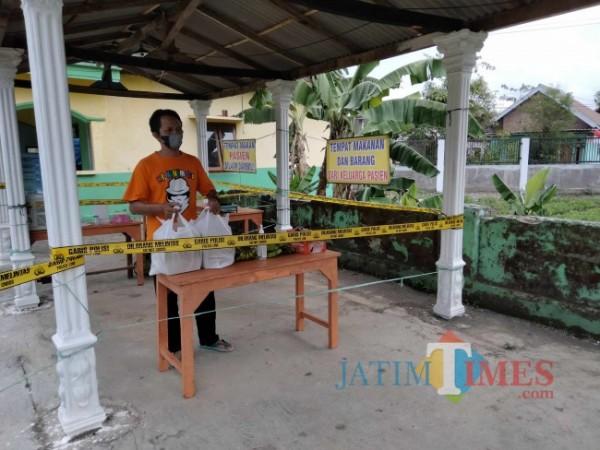 Salah satu pasien Covid-19 OTG yang sedang berada di isoter Desa Jatorejoyoso Kepanjen saat mengambil makan siang yang sudah disediakan petugas.(Foto: Riski Wijaya/MalangTIMES).