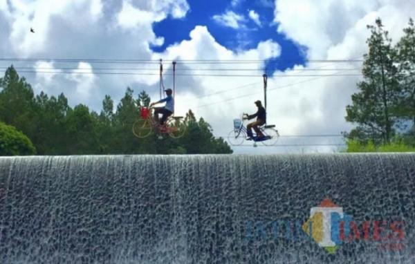 Beberapa wisatawan saat mengayuh sepeda di atas DAM Coban Talun. (Foto: Irsya Richa/MalangTIMES)