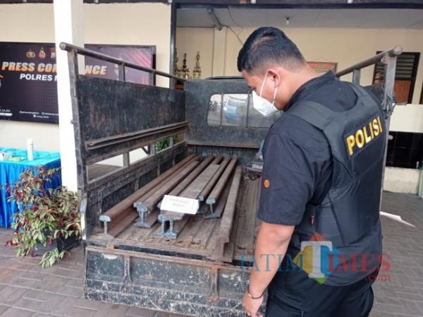 Polisi saat melihat barang bukti besi baja rel kereta api dan pikap yang digunakan untuk mengangkut (foto: Hendra Saputra/MalangTIMES)