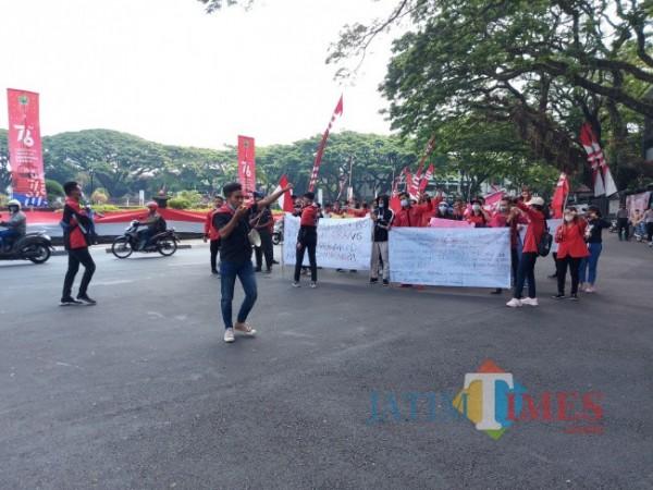 Puluhan massa aksi dari DPC GMNI Malang saat menggelar demonstrasi di depan Balai Kota Malang terkait peran pemerintah dalam menangani pandemi Covid-19, Jumat (20/8/2021). (Foto: Tubagus Achmad/MalangTIMES)