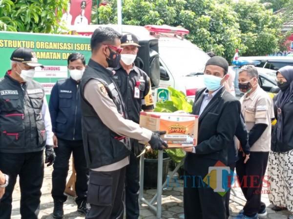 Manager Operasional BMH Jatim Gerai Malang, Lukman Hakim secara simbolis memberikan bantuan paket sembako kepada Forkopimda Kabupaten Malang yang kemudian diserahkan kepada warga (foto: Hendra Saputra/MalangTIMES)