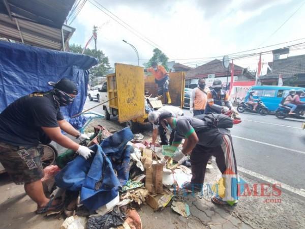 Warga bersama relawan yang gotong royong membawa barang-barang bekas tidak terpakai di kediaman Siswoyo untuk dibuang di Tempat Pembuangan Akhir (TPA) Supit Urang Malang, Sabtu (21/8/2021). (Foto: Tubagus Achmad/MalangTIMES)