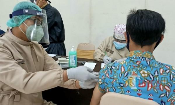 Tenaga kesehatan saat menyuntikkan vaksin kepada warga di Hotel Purnama beberapa saat lalu. (Foto: Irsya Richa/ MalangTIMES)