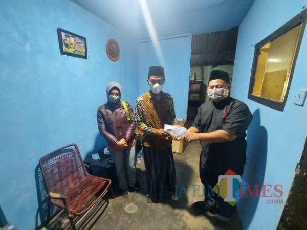 Wakil Ketua Fraksi Partai Keadilan Sejahtera (PKS) DPRD Kota Malang Trio Agus Purwono (baju hitam) saat memberikan bantuan kepada Siswoyo melalui Ketua RT 04 Sampurna Adi Wijaya, Sabtu (21/8/2021) malam. (Foto: Tubagus Achmad/ MalangTIMES)