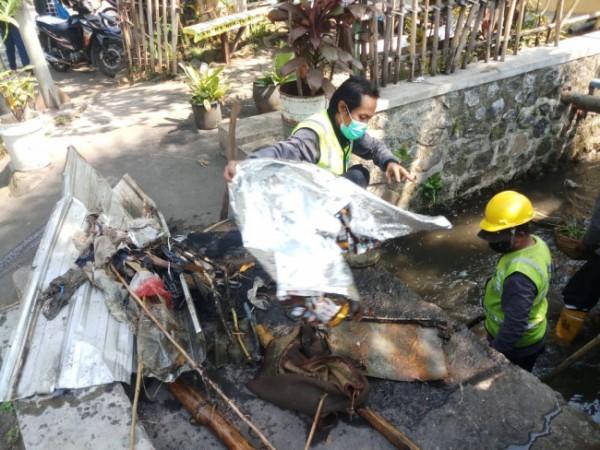 Nampak Satgas DPUPRPKP Kota Malang menemukan atap spandex hingga banner yang dibuang di saluran drainase (Ist)
