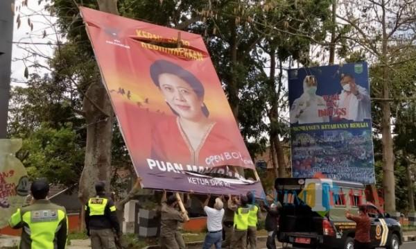 Ketua DPC PDIP Kota Batu Punjul Santoso memimpin pembongkaran baliho Puan Maharani bersama Satpol PP Kota Batu di Jalan Sultan Agung, Selasa (24/8/2021). (Foto: Irsya Richa/MalangTIMES)