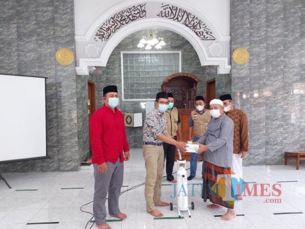 Direktur JatimTIMES Lazuardi Firdaus saat menyerahkan tabung oksigen kepada Dewan Penasehat Takmir Masjid Darul Muttaqin Selorejo Imam Syafii, Rabu (25/8/2021). (Foto: Tubagus Achmad/MalangTIMES)