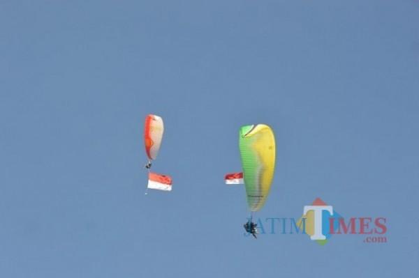 Cabor paralayang saat menerbangkan bendera merah putih di langit Kota Batu beberapa saat lalu. (Foto: Irsya Richa/MalangTIMES)