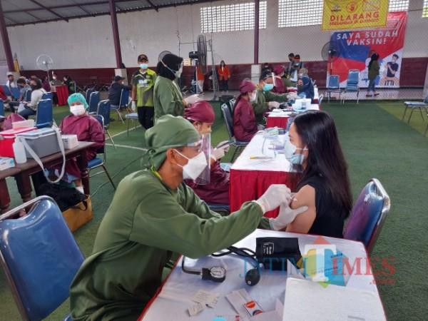 Salah satu peserta vaksinasi yang menjalani penyuntikan Vaksin Covid-19 jenis Sinovac oleh vaksinator dari Detasemen Kesehatan Wilayah Kesdam V/Brawijaya di STIE Malang Kucecwara, Kamis (26/8/2021). (Foto: Tubagus Achmad/JatimTIMES)