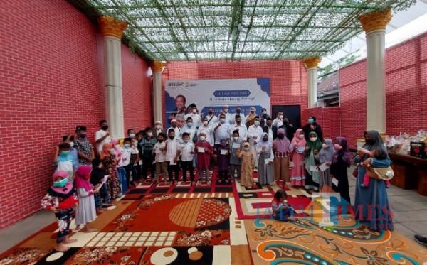 Suasana foto bersama jajaran pengurus MES (Masyarakat Ekonomi Syariah) dengan puluhan anak yatim piatu di Rumah Makan Ocean Garden Kota Malang, Jumat (27/8/2021). (Foto: Tubagus Achmad/JatimTIMES)