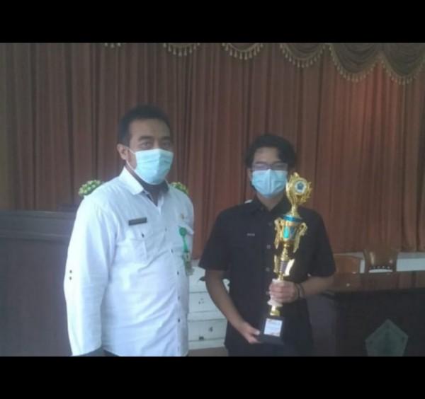 Andikasatria Wicaksana Putra (kanan) remaja 14 tahun Kota Malang saat menerima penghargaan lomba pembuatan film dengan tema Covid-19. (Foto: Istimewa).