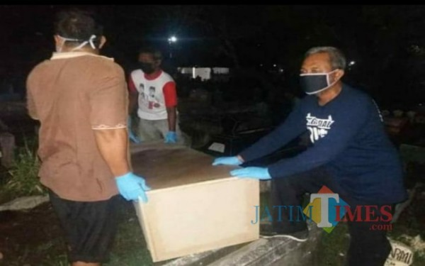 Haris Mukti Anshory Kaos Biru saat memakamkan jenazah pasien Covid-19 malam hari / Foto : Istimewa / Tulungagung TIMES