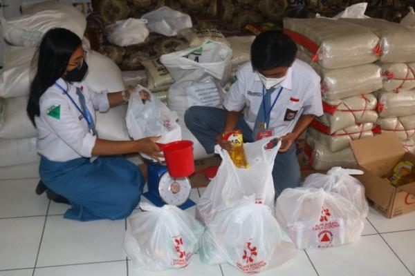 Moura Eka Sandrina (kiri) dan Ifron Petrus Andries (kanan), aktivitas dua siswa SMA di Malang yang menjadi relawan Covid-19 saat menata sembako untuk dibagikan kepada warga terdampak Covid-19. (Foto: istimewa).