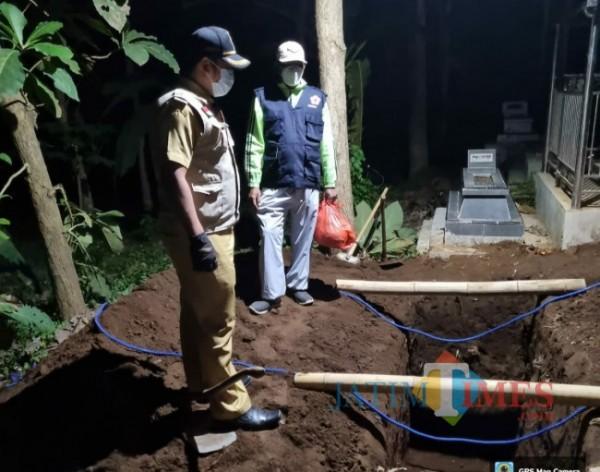 Lurah Dampit, Agus Setia Budi saat memantau persiapan pemakaman jenazah pasien Covid-19 di wilayahnya.(Foto: Riski Wijaya/ MalangTIMES).