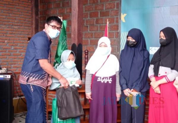 Owner Koberbar, Dodiet Arya Mahendra saat memberikan bantuan kepada anak yatim korban covid dan dhuafa (foto: Hendra Saputra/MalangTIMES)