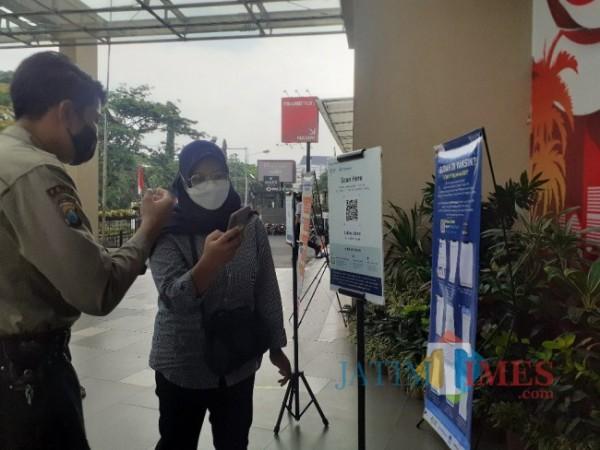 Salah satu pengunjung Mal di Kota Malang saat akan masuk untuk melakukan scan barcode PeduliLindungi. (Arifina Cahyanti Firdausi/MalangTIMES).