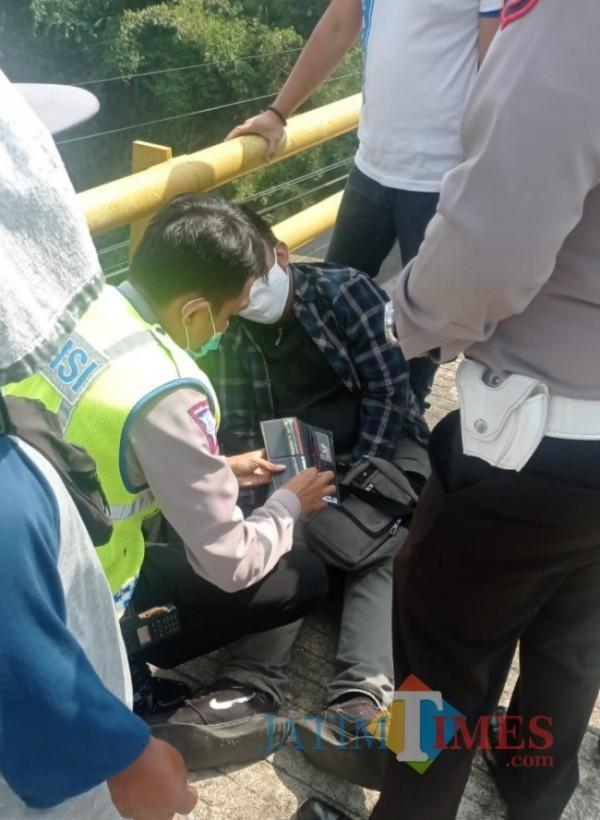 Sosok mahasiswa berinisial MS (22) yang melakukan percobaan bunuh diri saat dievakuasi oleh pihak kepolisian dan pengebdara yang melintas di jalur pejalan kaki Jembatan Suhat sisi barat, Rabu (1/9/2021). (Foto: Hendra Saputra/JatimTIMES)