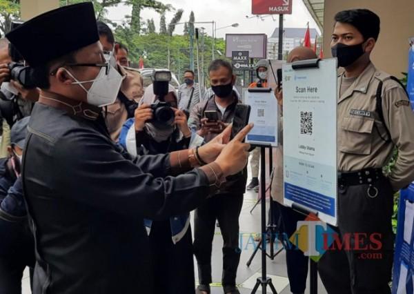 Wali Kota Malang Sutiaji saat melakukan scan barcode aplikasi peduli lindungi untuk masuk ke salah satu Mal di Kota Malang. (Arifina Cahyanti Firdausi/MalangTIMES).