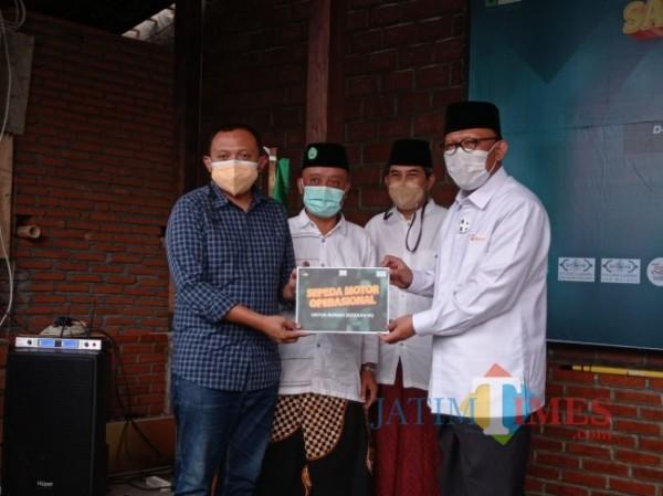 Rektor Unisma, Prof Dr Maskuri Bakri secara simbolis memberikan sepeda motor untuk Rumah Sedekah NU (Hendra Saputra/MalangTIMES)