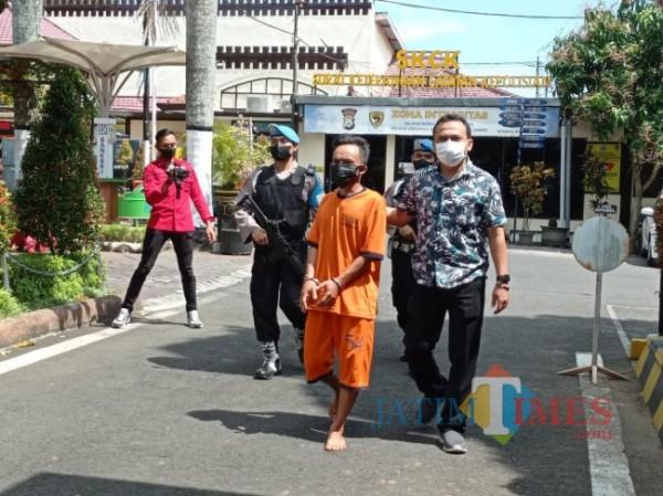Tersangka TB (baju orange) saat digelandang anggota Polres Malang (foto: Hendra Saputra/ MalangTIMES)