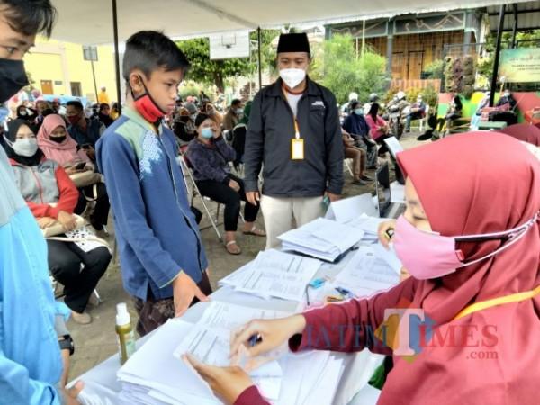 Kepala SMK Terpadu Al Islahiyah, Muhammad Nasrulloh saat meninjau proses pelaksanaan vaksinasi.(Foto:Riski Wijaya/MalangTIMES).