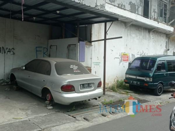 Kondisi mobil sedan dengan nomor polisi N-1367-CX yang ban mobilnya telah hilang dicuri maling, Senin (6/9/2021). (Foto: Tubagus Achmad/JatimTIMES)