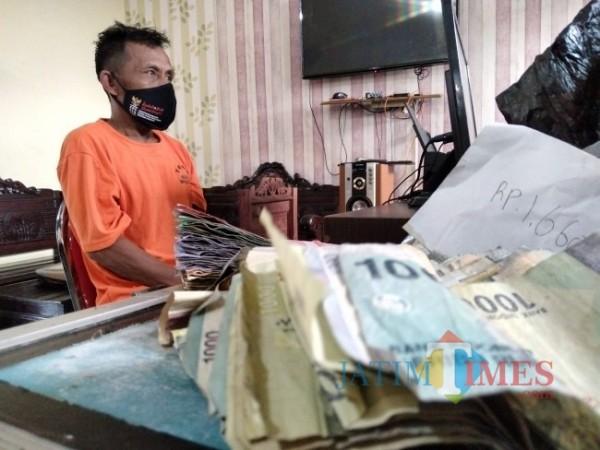 Tersangka Paiman bersama barang bukti sejumlah uang hasil curiannya. (Foto:Riski Wijaya/MalangTIMES)