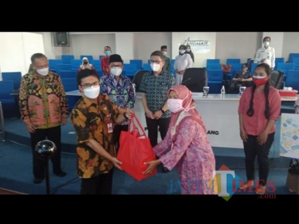 Penyaluran paket bantuan sosial oleh Diskopindag Kota Malang kepada masyarakat terdampak PPKM secara simbolis di momen peringatan Hari Koperasi Nasional ke 74, Selasa (7/9/2021). (Arifina Cahyanti Firdausi/MalangTIMES).$^