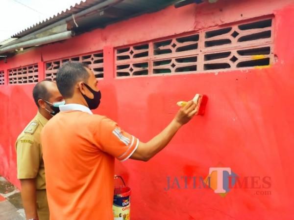 Petugas menghapus mural berbau kritik.(Foto : Team JATIMTIMES)