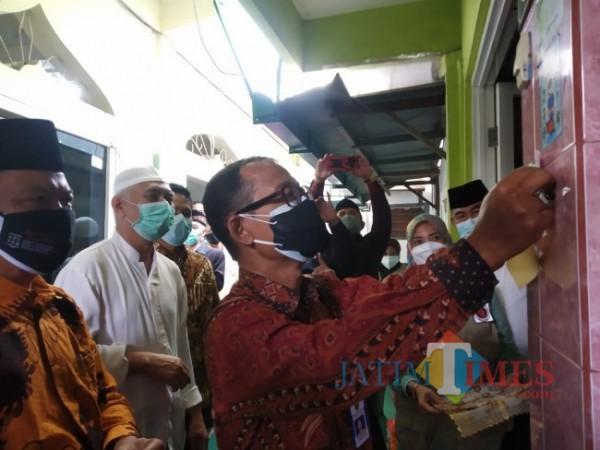 Camat Klojen, Drs Heri Sunarko saat menempelkan stiker informasi data vaksin warga (Anggara Sudiongko/MalangTIMES)