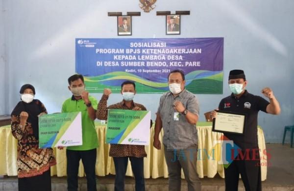 Kepala BPJS Ketenagakerjaan Kediri Suharno Abidin menyerahkan secara simbolis kepesertaan kepada peserta. (eko arif s/Jatimtimes)