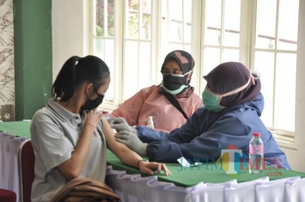 Tenaga kesehatan saat melakukan vaksinasi Covid-19 kepada warga di Kota Batu beberapa saat lalu. (Foto: Irsya Richa/MalangTIMES)