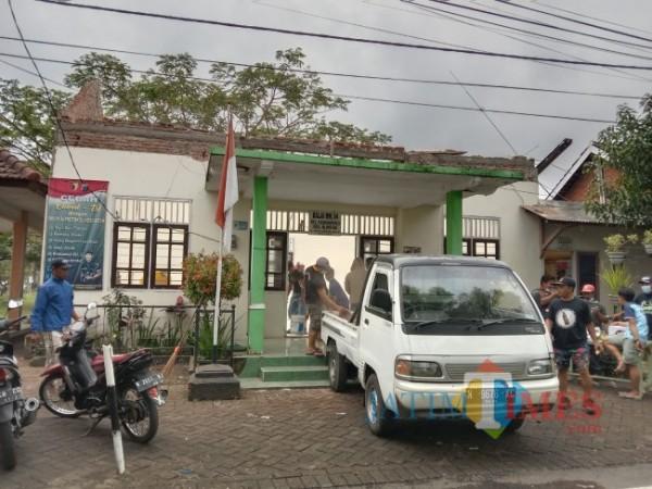 Warga setempat saat bergotong-royong membersihkan puing-puing reruntuhan atap Balai RW 04 Kelurahan Pandanwangi, Kecamatan Blimbing, Kota Malang, Minggu (12/9/2021). (Foto: Tubagus Achmad/JatimTIMES)