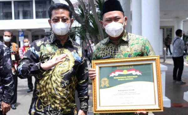 Bupati Gresik Fandi Akhmad Yani menunjukkan piagam penghargaan, Senin (13/9/2021). (Foto : Syaifuddin Anam/GresikTimes)