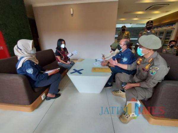 Petugas Badan Pendapatan Daerah (Bapenda) Kota Malang bersama Satpol PP Kota Malang saat melakukan penindakan kepada sejumlah hotel dan restoran yang tunggak pajak, Senin (13/9/2021). (Foto: Tubagus Achmad/JatimTIMES)